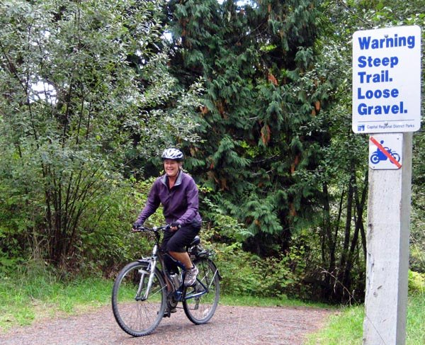 A skilled cyclist gives a grin of delight as she makes it up this steep hill on the Galloping Goose Trail