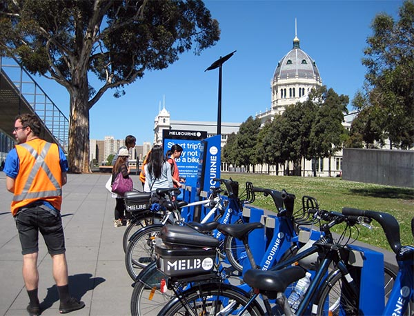 A lot of the Melbourne Bike Share stations are at tourist hot spots - yet not many of them are actually used - Could it be because tourists such as the ones in the photo don't travel with helmets in their purses?