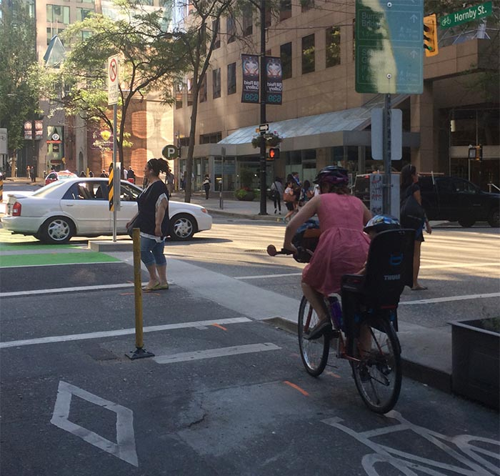 Mother cycling through the center of Vancouver with her toddler, using the separated bike lanes. Vancouver Bike Share