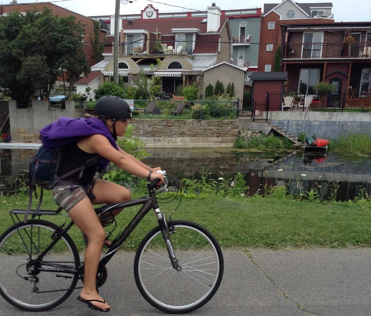 Montreal architecture visible in the background behind this cyclist on the Lachine Canal Bike Path