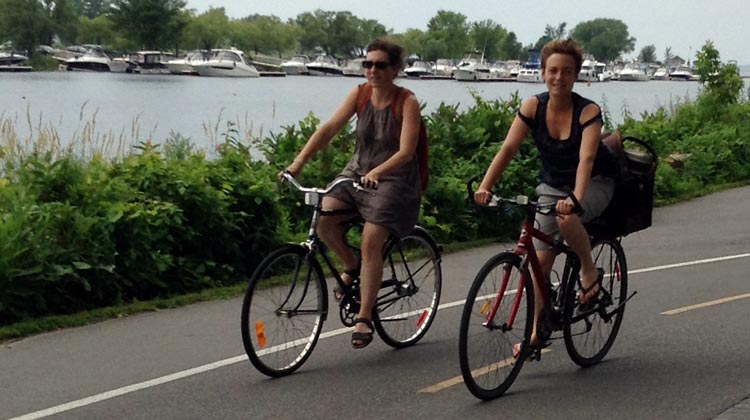 Cyclists enjoy the wind in their hair on the Lachine Canal Bike Path in Montreal