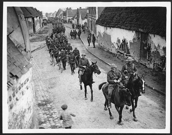 The Newfoundland Regiment marching back to billet after Monch - on horses and bikes