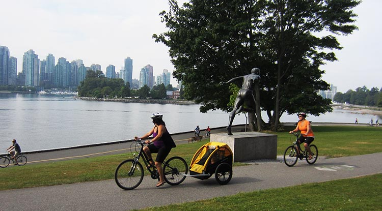 People cycling past the Harry Jerome statue on the Stanley Park Seawall Bike trail
