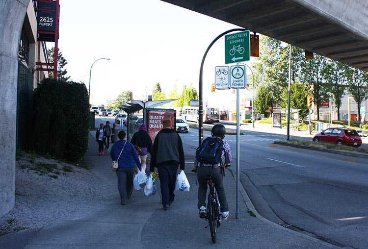 The approach to the Rupert Skytrain Station is just plain stupid. There's a bus stop, a bike route, milling pedestrians, a blind corner, a crosswalk - all thrown together with no planning and no guidance. As a result, it's down to cyclists being super careful to avoid accidents. Here, a cyclist prepares to dodge around the bus stop to avoid hitting pedestrians. Joe has had a head-on collision with another cyclist in this spot. Recently, someone has thrown in a load of gravel (on the left) to add slipping as an extra danger to avoid!