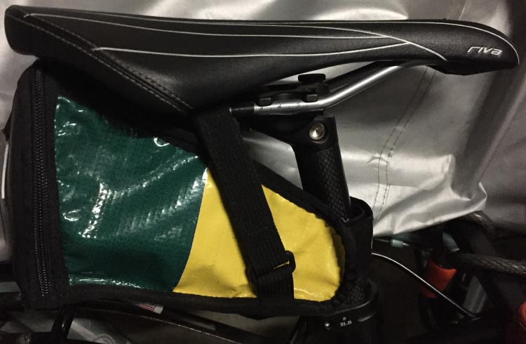 This is the saddle bag I use. It tucks neatly under my saddle, and my emergency kit fits into it
