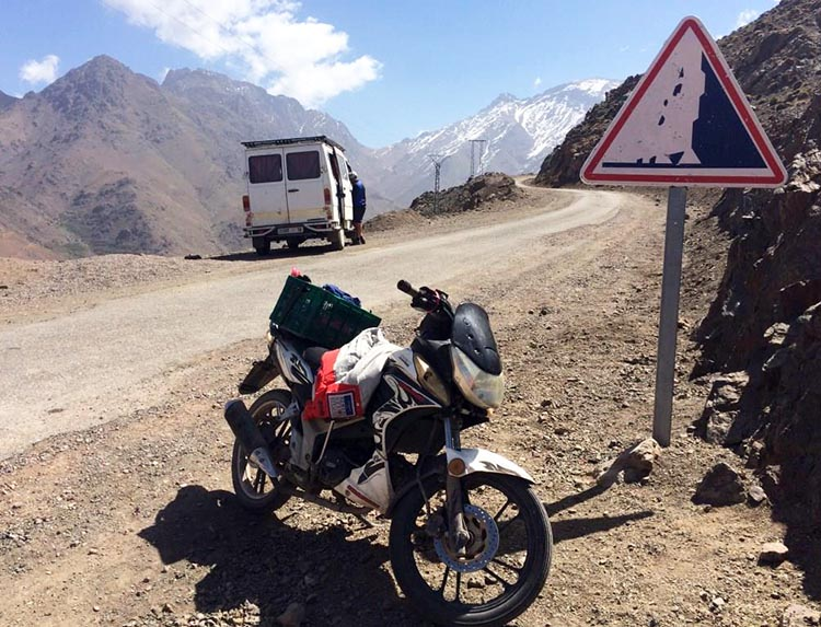 Cycling in the Atlas Mountains in Morocco. We arrive at a small remote café, where there is a motorbike parked