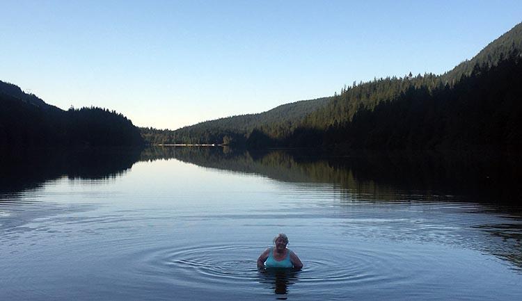 Cycling near Buntzen Lake, British Columbia, Canada. Maggie swimming in Buntzen Lake at North Beach