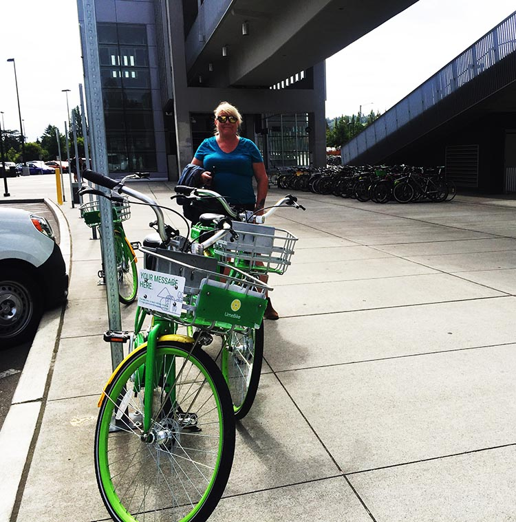 Lime Bikes and Scooters for Shared Transport Options. We often rode Lime bikes to transit stations, and then took transit. Here's Maggie with the bikes we rode to the University of Washington light rail station. It was a whole lot easier parking the bikes than trying to park a car!