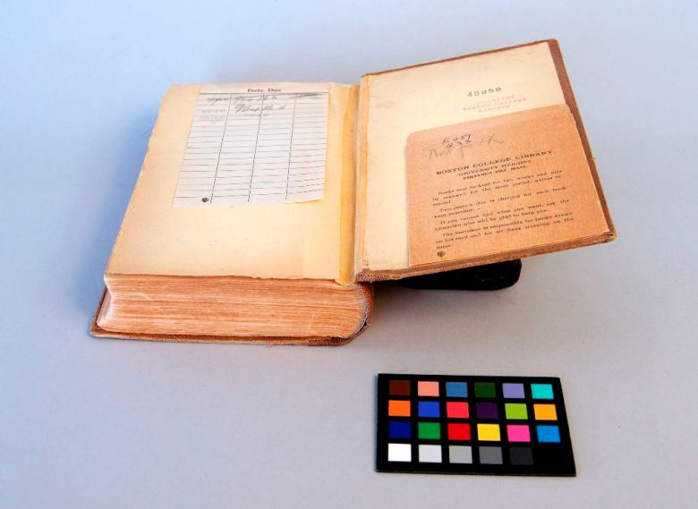 Brown cloth binding with yellow endpapers and library checkout card, showing joint repaired with toned tissue