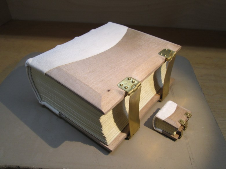 Gothic-inspired binding with shaped wooden boards, alum-tawed pigskin spine inset into board, and inset brass clasps, with fifth-scale model