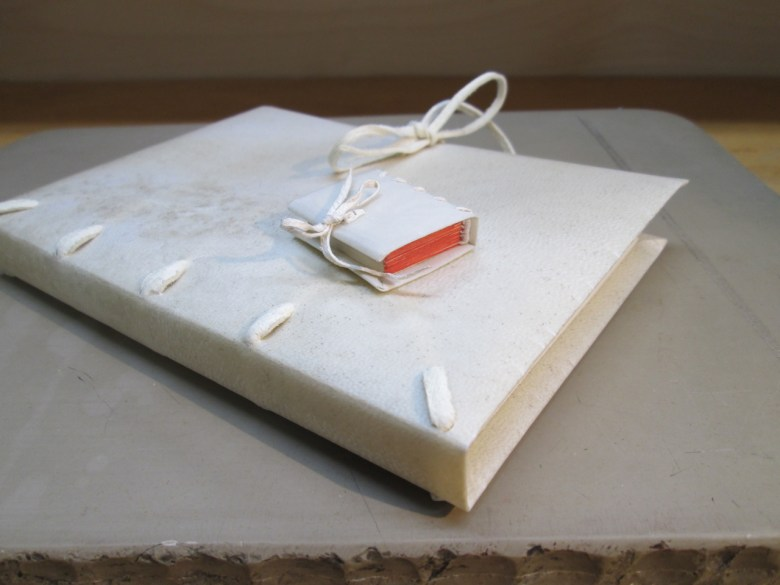 Vellum binding with alum-tawed pig thongs and foredge ties, with fifth-scale model in uterine calf with red painted edge.