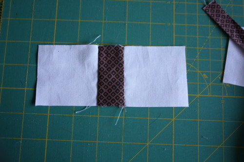Sew the white rectangles to the brown rectangle right sides together and press the seam allowances.