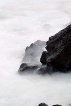 black ocean rocks, waves white mist