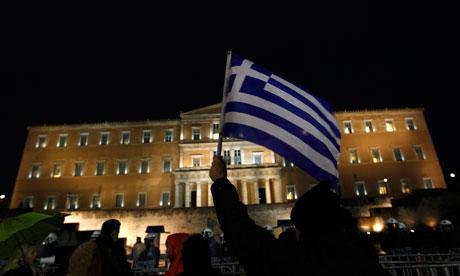 Um manifestante levanta uma bandeira grega durante uma manifestação anti-autoridade diante do Parlamento em Atenas.. Crédit photo : Yannis Behrakis/Reuters