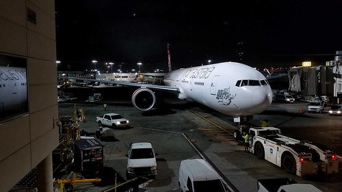 Boeing 777 parked at the airport gate at night.