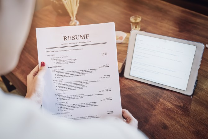 woman holding resume with tablet in background