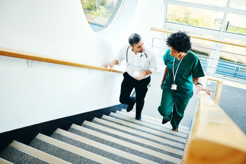 Two healthcare professionals walking up the stairs and talking