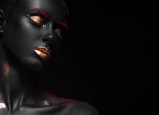 photo of woman with dark skin wearing gold eyeshadow and lipstick looking down while against black background