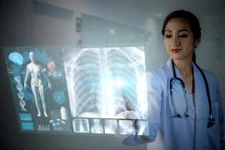 young medical professional using clear tablet to study x-ray and other medical data