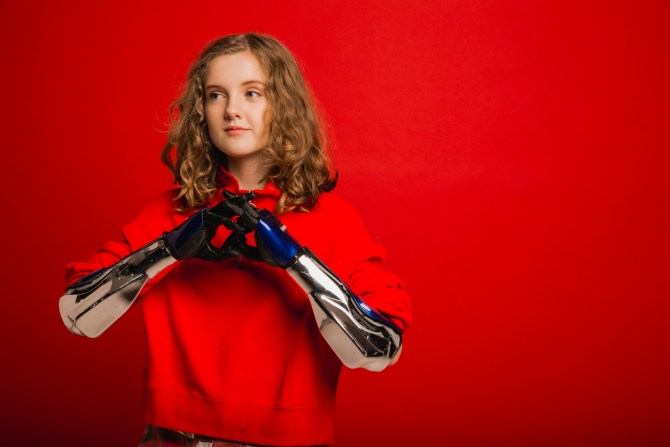 girl with curly blonde hair wearing red hoodie against red background holding prosthetic hands and arms together