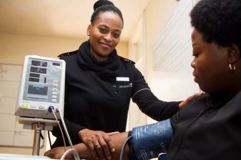 woman using machine to take blood pressure of seated woman indoors
