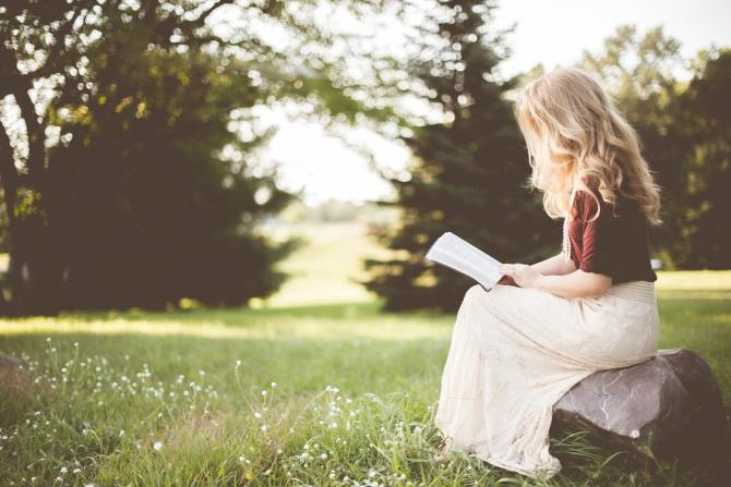 woman-with-blonde-hair-wearing-red-top-and-long-white-skirt-sitting-on-rock-in-meadow-while-reading-book