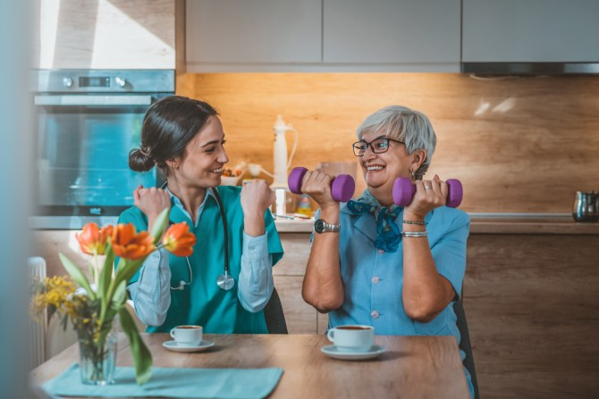senior-woman-doing-dumbbell-curls-with-physical-therapist-at-kitchen-table-with-teacups-and-vase-of-orange-flowers