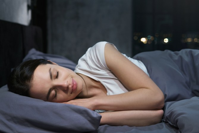 woman-with-dark-hair-sleeping-on-side-in-bed-with-muted-dark-blue-linens