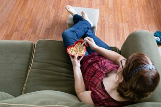 overhead-view-of-woman-sitting-on-sofa-with-feet-on-footrest-while-holding-heart-shaped-bowl-of-cheerios-with-spoon