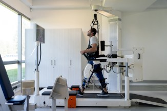 A man doing physical therapy by using an exoskeleton to walk on a treadmill