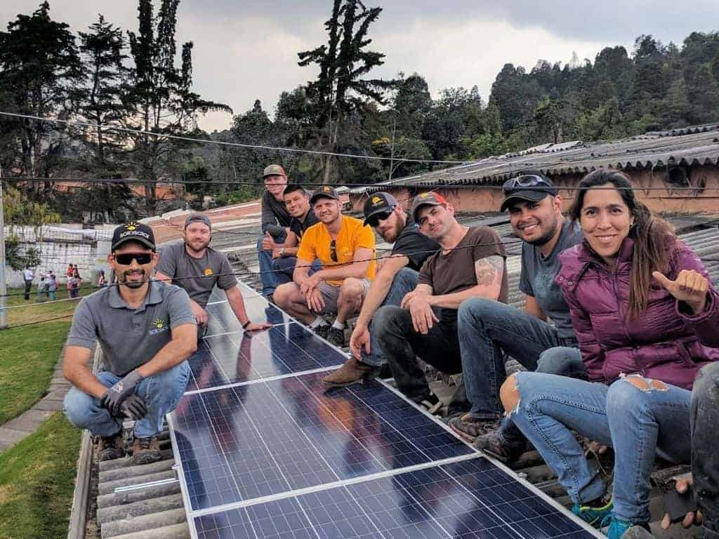 Smiling employees surrounding a completed solar PV array in Bogota.