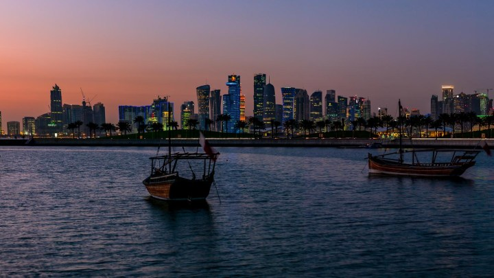 Doha FIFA 2020 Skyline of Doha photographed on night time view from the Corniche promenade. In the forground the traditional Dhow boat.