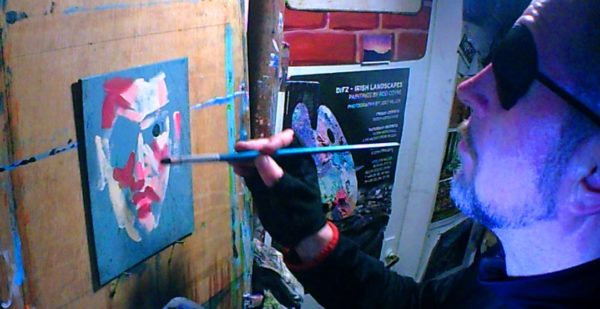 Rod tests painting a self portrait on a small scale with one eye.