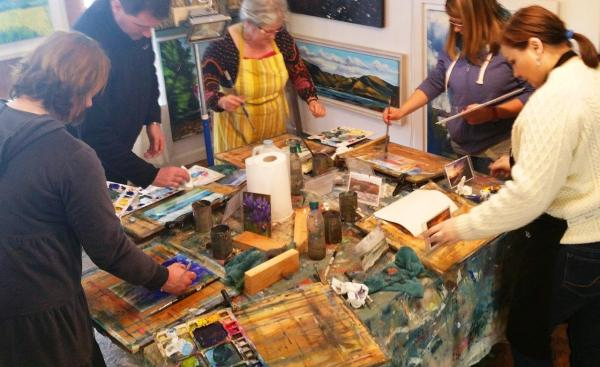 Five painting students working at one big table.
