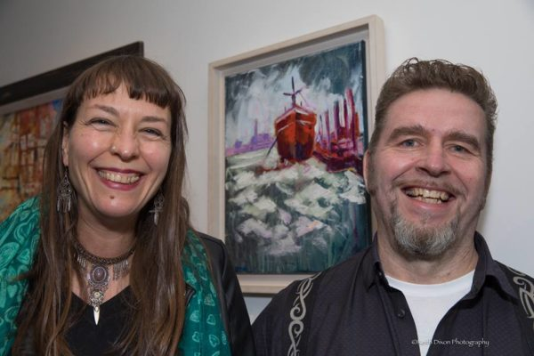 "Anja & Rod Coyne grinning in front of Rod's ""Red Hull"" painting at the official (pardon the pun) launch. Photo by Keith Dixon."