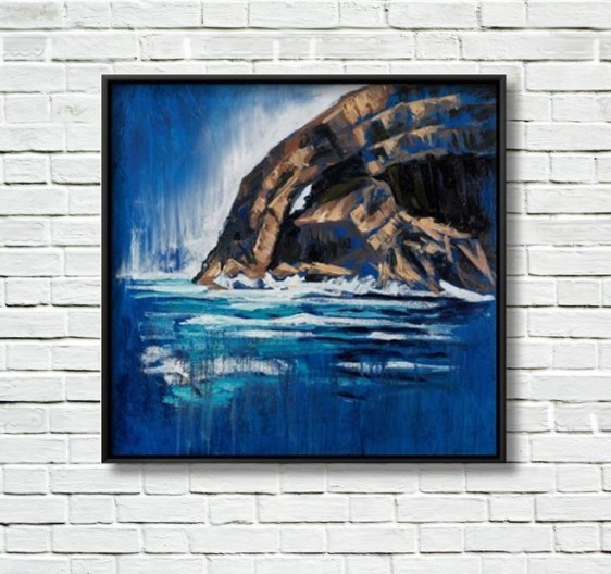 Skellig Arch canvas print displayed in a black frame on a white brick wall.