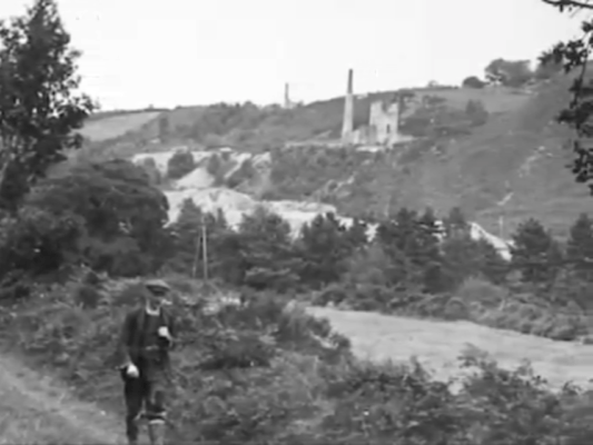 An antique photo shows a A miner marches to the next shift with two Williams engine houses and chimney stacks in the distance.