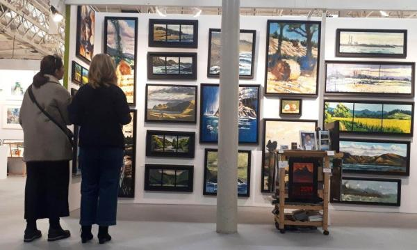 Rod Coyne's stand at 2018 Art Source be apprised by two keen fans.