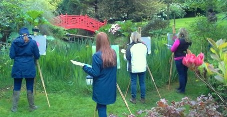 Photo depicting students set about capturing the red Japanese bridge nesting in lush greens at our Workshop at Knockanree Gardens in 2019.