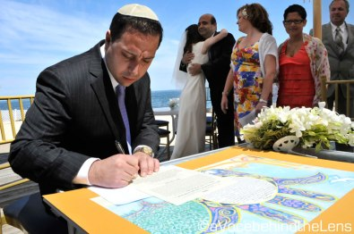I like this photograph for a few reasons: you can see how detailed the Ketubah is, the husband is seen signing the Ketubah, and the bride is in the background overwhelmed by happiness on her wedding day.