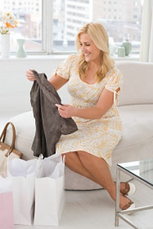 a woman smiling as she looks through her newly purchased clothes