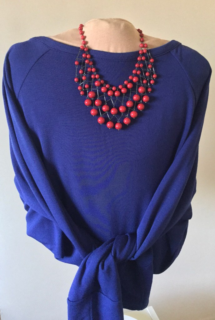 blue top on mannequin with red bead necklace