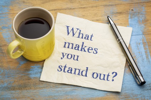 "A note beside a yellow mug of coffee says ""What makes you stand out?"""