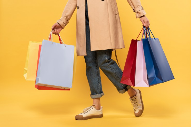 person dressed in jeans and jacket carrying colourful shopping bags