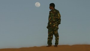 A Sahrawi man dressed in military clothes waits for sunset at the Sahara desert at a refugee camp in Dakhla, near Tindouf in southwestern Algeria April 18, 2008. Picture taken on April 18, 2008. REUTERS/Dani Cardona (ALGERIA) - RTR1ZNGH