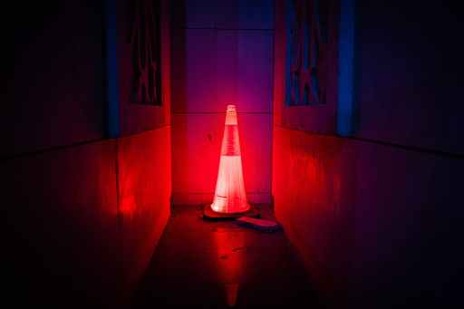 Glowing red traffic cone in dark alley. Check out these red flags that reveal big egos.