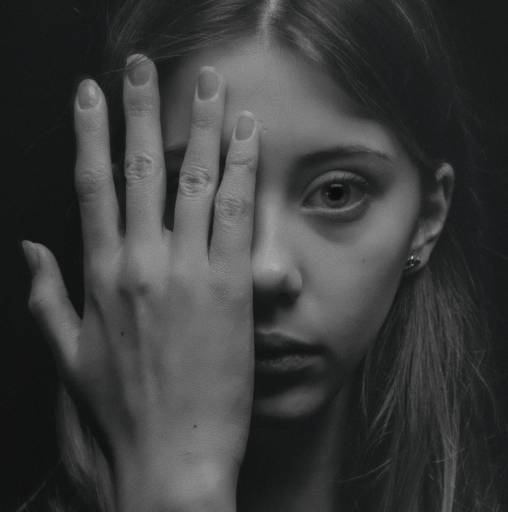 Grayscale photo of female empath looking at you while covering her right eye with her right hand.