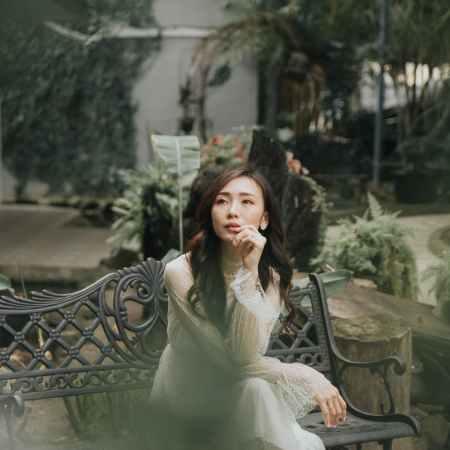 elegant dreamy asian woman on bench in garden