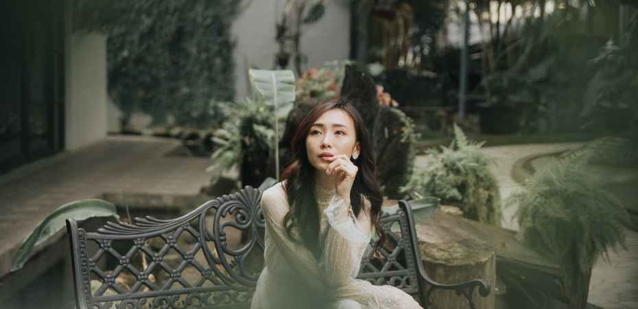 elegant dreamy asian woman on bench in garden