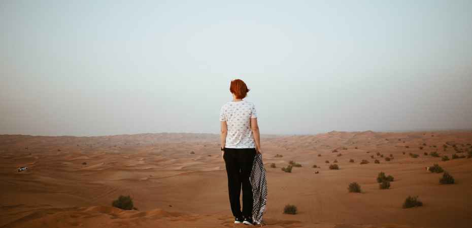 unrecognizable woman in endless desert in overcast